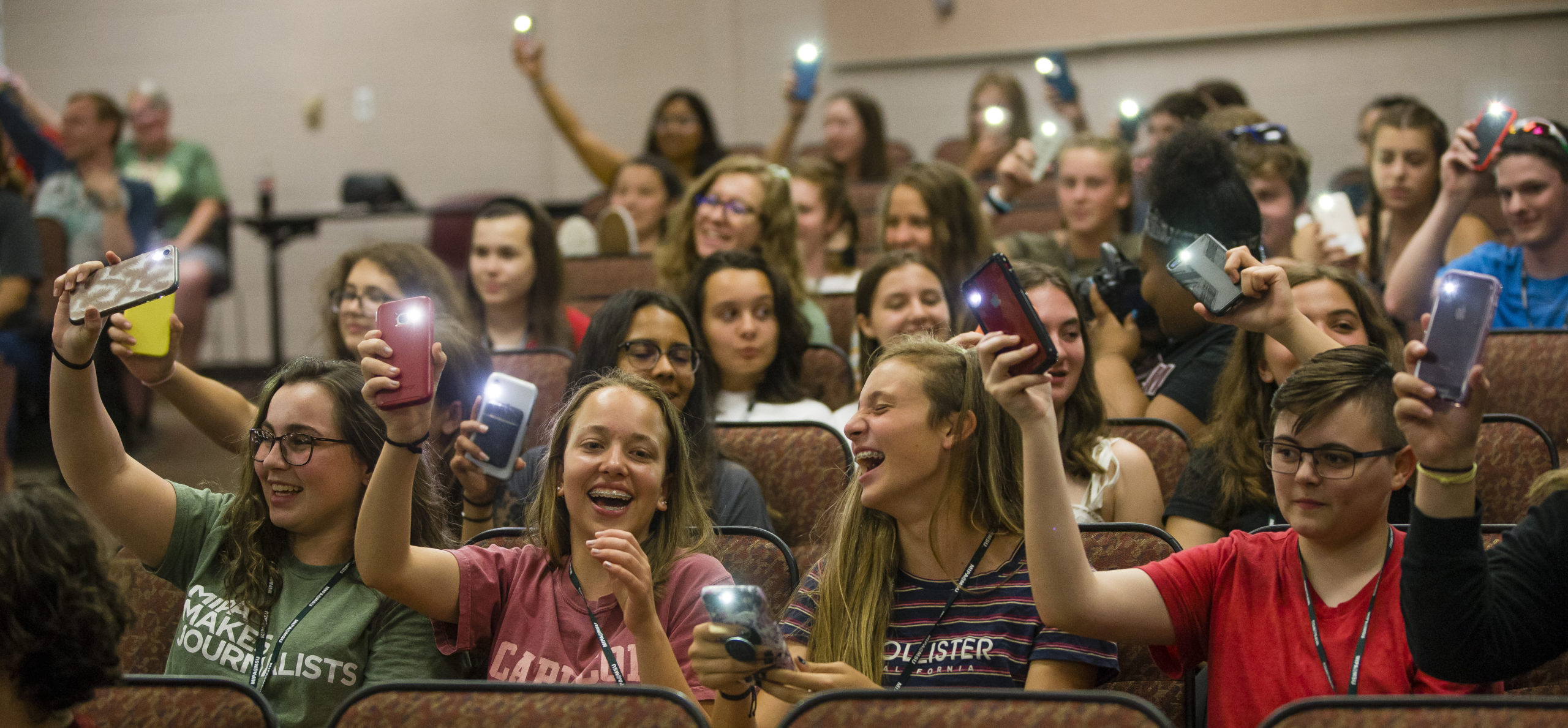 Participants hold up their phones with the flashlight on during the MIPA's Got Talent variety show during the 2019 MIPA Summer Journalism Workshop.
